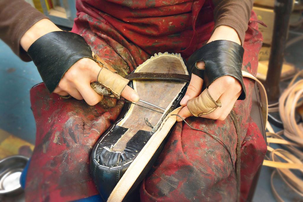 Eine Person arbeitet an einem Schuh.
