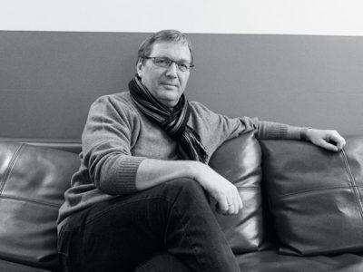 Ein Mann mit Brille sitzt auf einem Ledersofa.