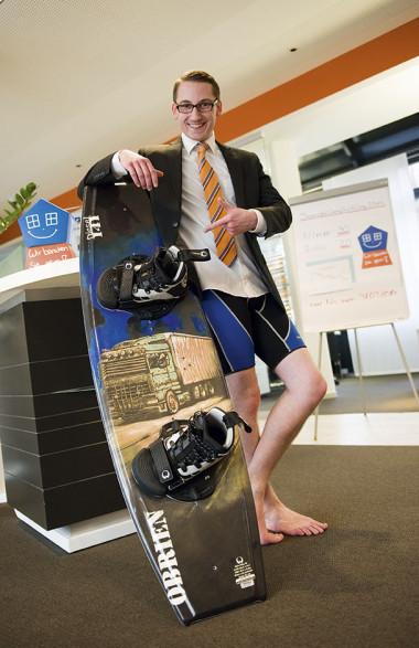 Ein junger Mann steht in Jacket und Badehaose mit seinem Wakeboard in einer Bankfiliale.