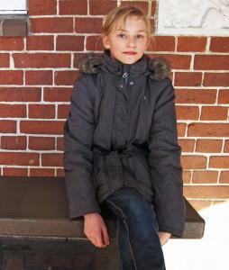 Eine blonde Schülerin sizt auf einer Bank im Freien.