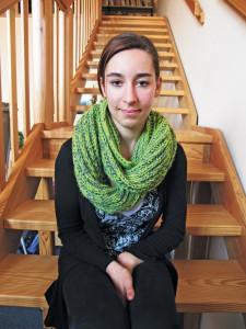 Eine Schülerin mit grünem Schal sitzt auf einer Holztreppe.