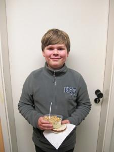 Ein Jugendlicher steht vor einer Tür und ächelt in die Kamera.