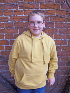 Ein Jugendlicher im gelben Pulli steht lächeln vor einer Backsteinmauer.