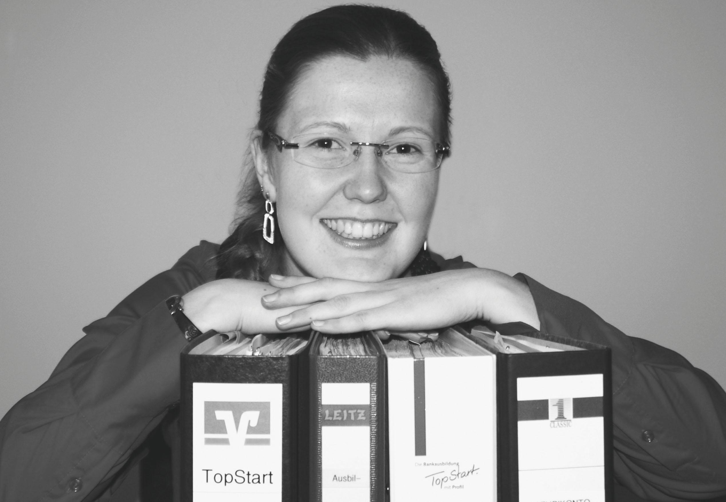 Eine junge Frau stützt ihr Kinn auf Ordner und lächelt in die Kamera.