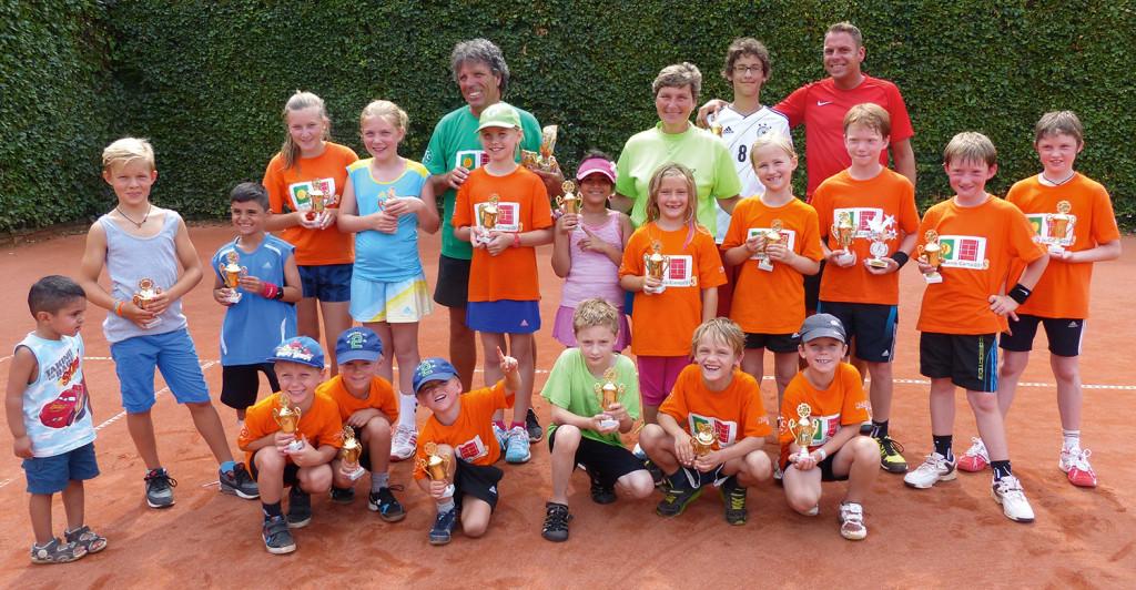 Kinder und Erwachsende auf einem Tennisplatz.