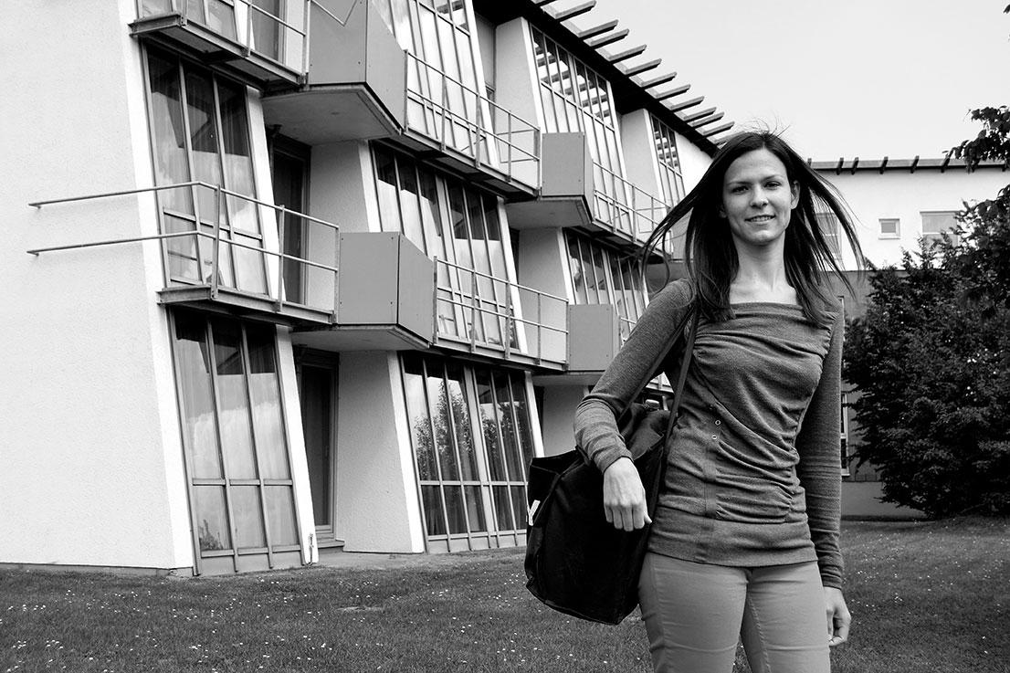 Eine junge Frau vor einem Gebäuse.