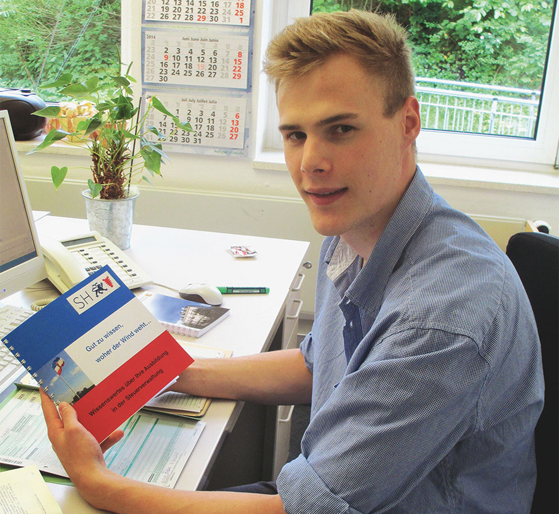 Ein blonder junger Mann im blauen Hemd sitzt am Schreibtisch.