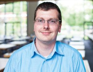 Ein Mann im blauen Hemd lächelt in die Kamera.