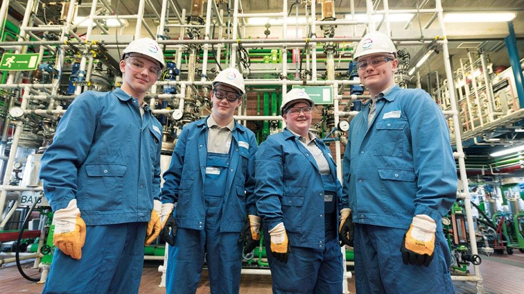 Vier junge Menschen in Arbeitskleidung stehen in einem Chemiewerk und lächeln in die Kamera.