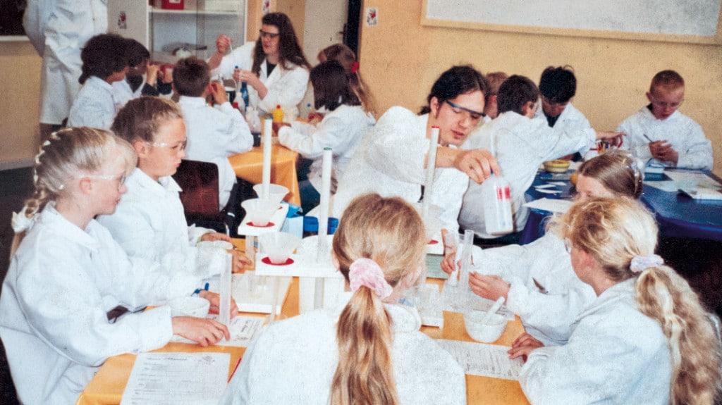 Kinder in Laborkitteln experimentieren.