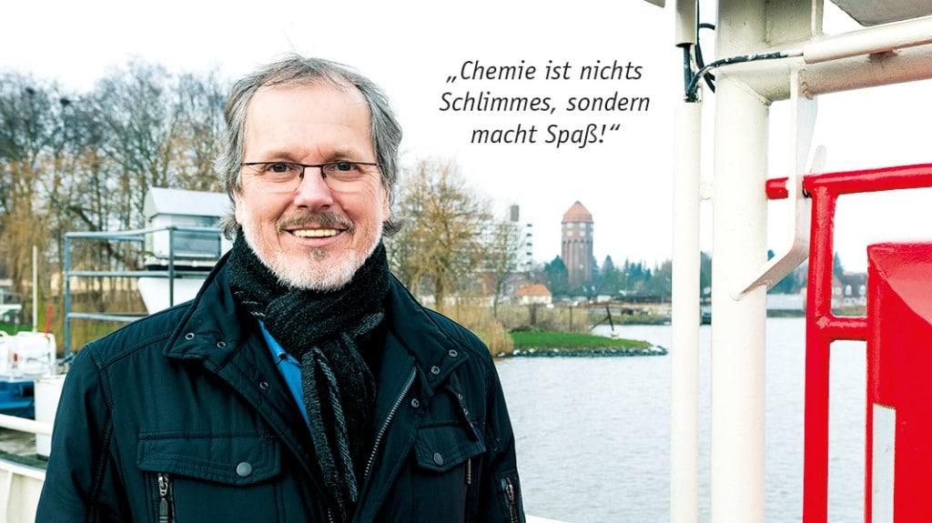 Ein Mann mit Brille und Bart lächelt in die Kamera.