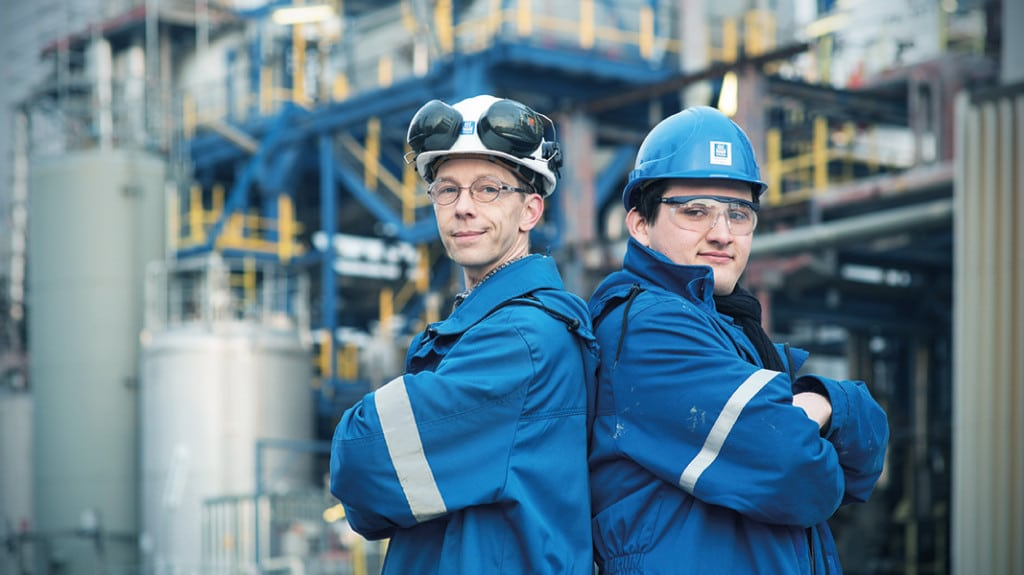 Ein junger und ein älterer Mann in blauer Arbeitskleidung stehen Rücken an Rücken und blicken in die Kamera.