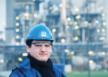 Ein junger Mann in blauer Arbeitskleidung steht vor einem Chemiewerk.