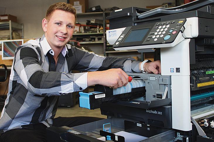 EIn junger Mann arbeitet an einem Kopierer und lächelt in die Kamera.
