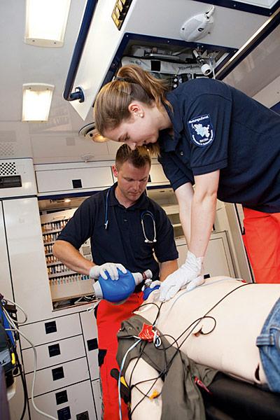 Zwei auszubildende Notfallsanitäter üben an einer Puppe.