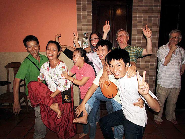 Jugendliche und Erwachsene lachen ausgelassen in die Kamera.