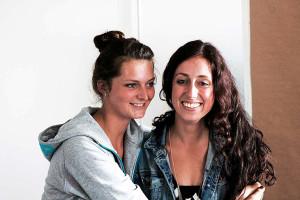 Zwei junge Frauen umarmen sich und lachen.