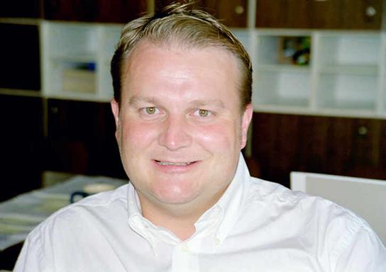 Ein Mann in weißem Hemd lächelt in die Kamera.