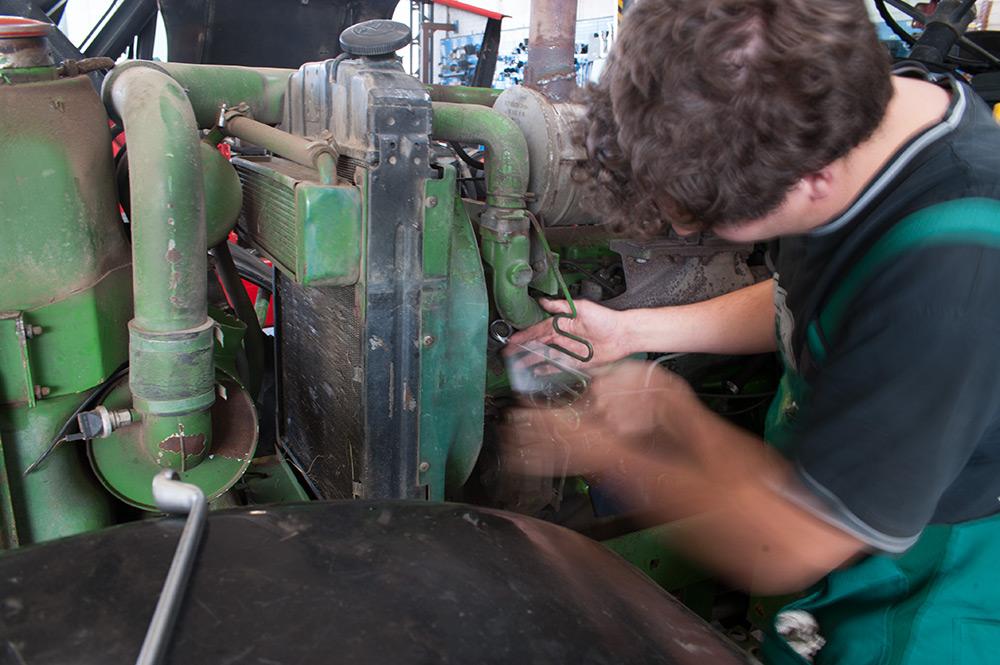 Ein Mann arbeitet mit Werkzeug am Heck eines Traktors.