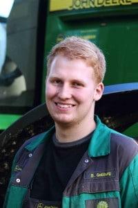 Ein junger Mann in Arbeitskleidung steht lächelnd vor einem Traktor.