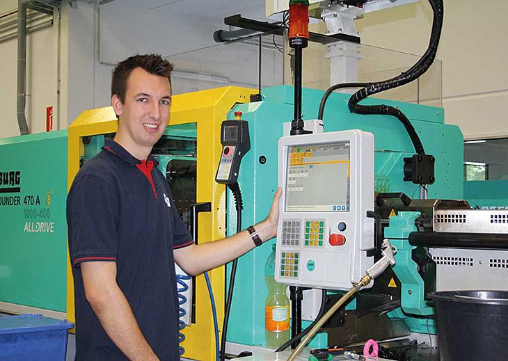 Ein junger Mann steht an einer Maschine und lächelt in die Kamera.