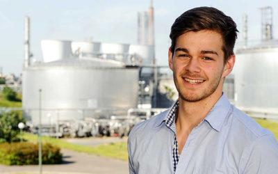 Ein junger Mann im blauen Hemd steht vor einem Fabrikgelände.