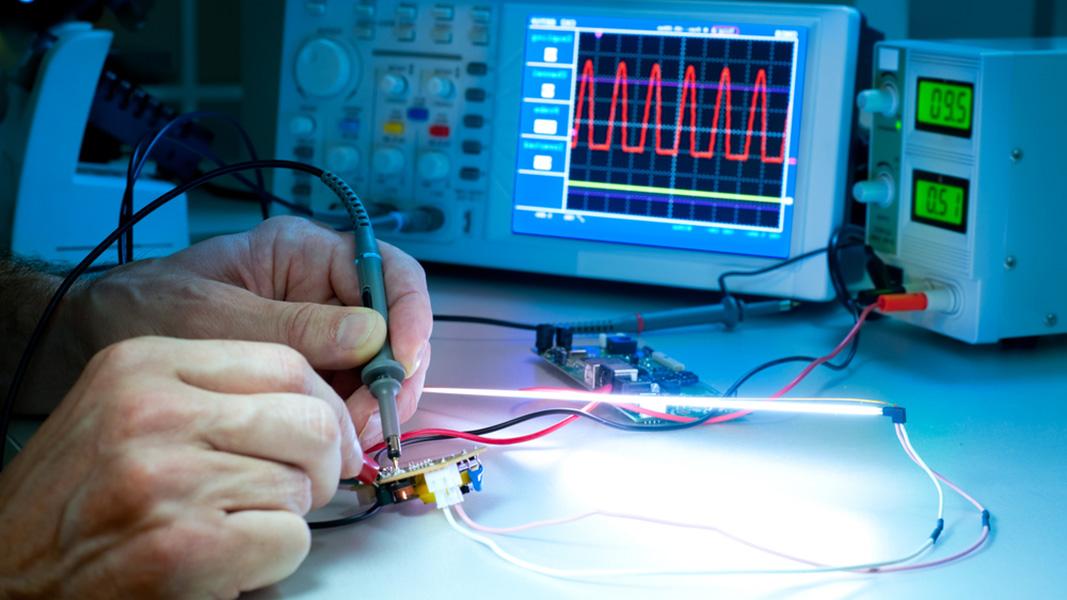 Zwei Hände vor einem elektronischen Bildschirm.