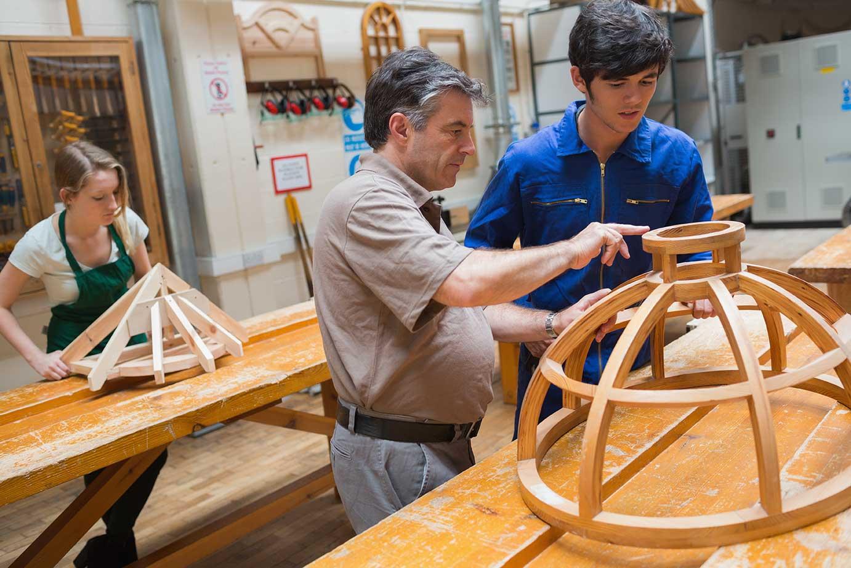 Mehrere Personen verarbeiten Holz.