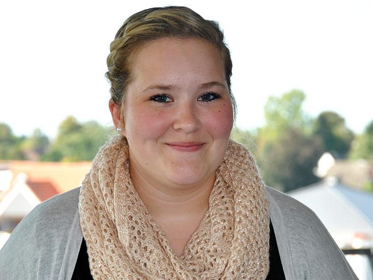 Eine blonde junge Frau mit Schal.