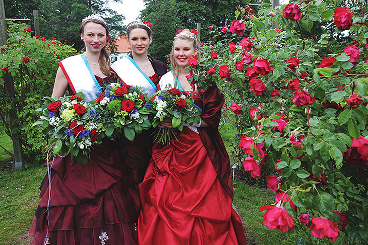 Drei junge Frauen in Kleidern und mit Rosensträußen lassen sich fotografieren.