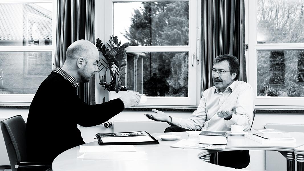 Zwei Männer unterhalten sich an einem Tisch.