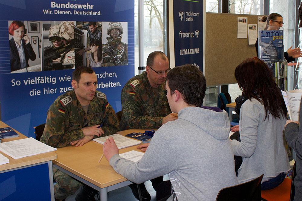 Schülerinnen und Schüler lassen sich von Soldaten der Bundeswehr beraten.