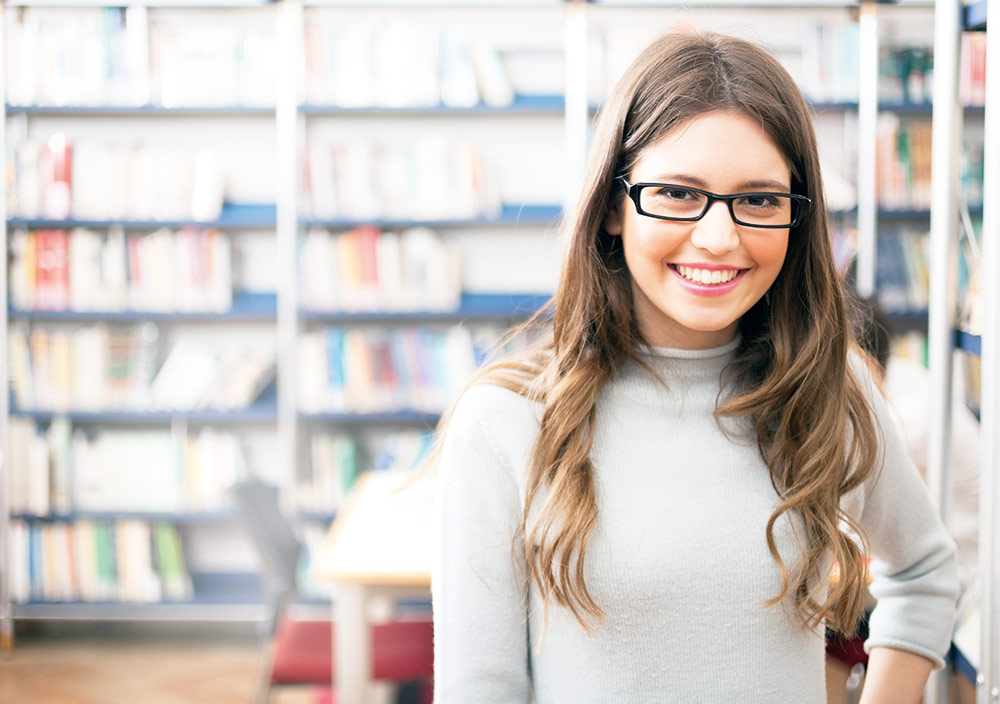 Eine junge frau mit langen Haaren und Brille lächelt in die Kamera.