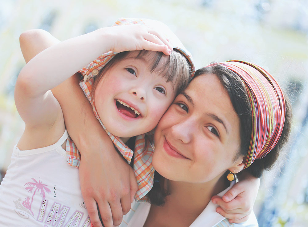 Eine junge Frau und ein Kind lachen in die Kamera.
