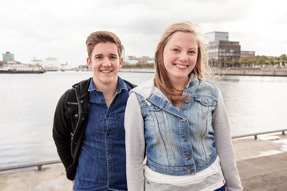 Zwei junge Menschen stehen vor einem Gewässer und lächeln in die Kamera.