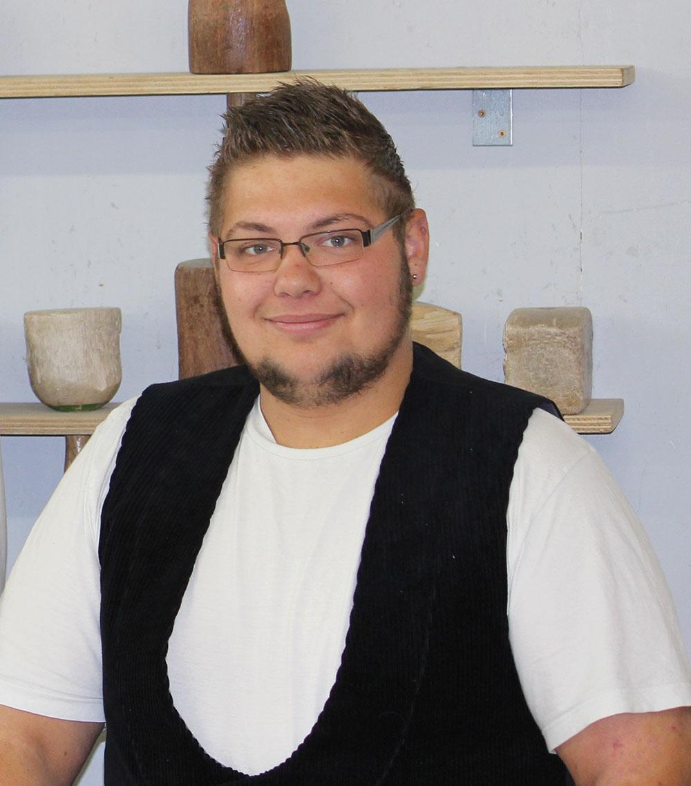 Ein junger Mann in Arbeitsweste lächelt in die Kamera.