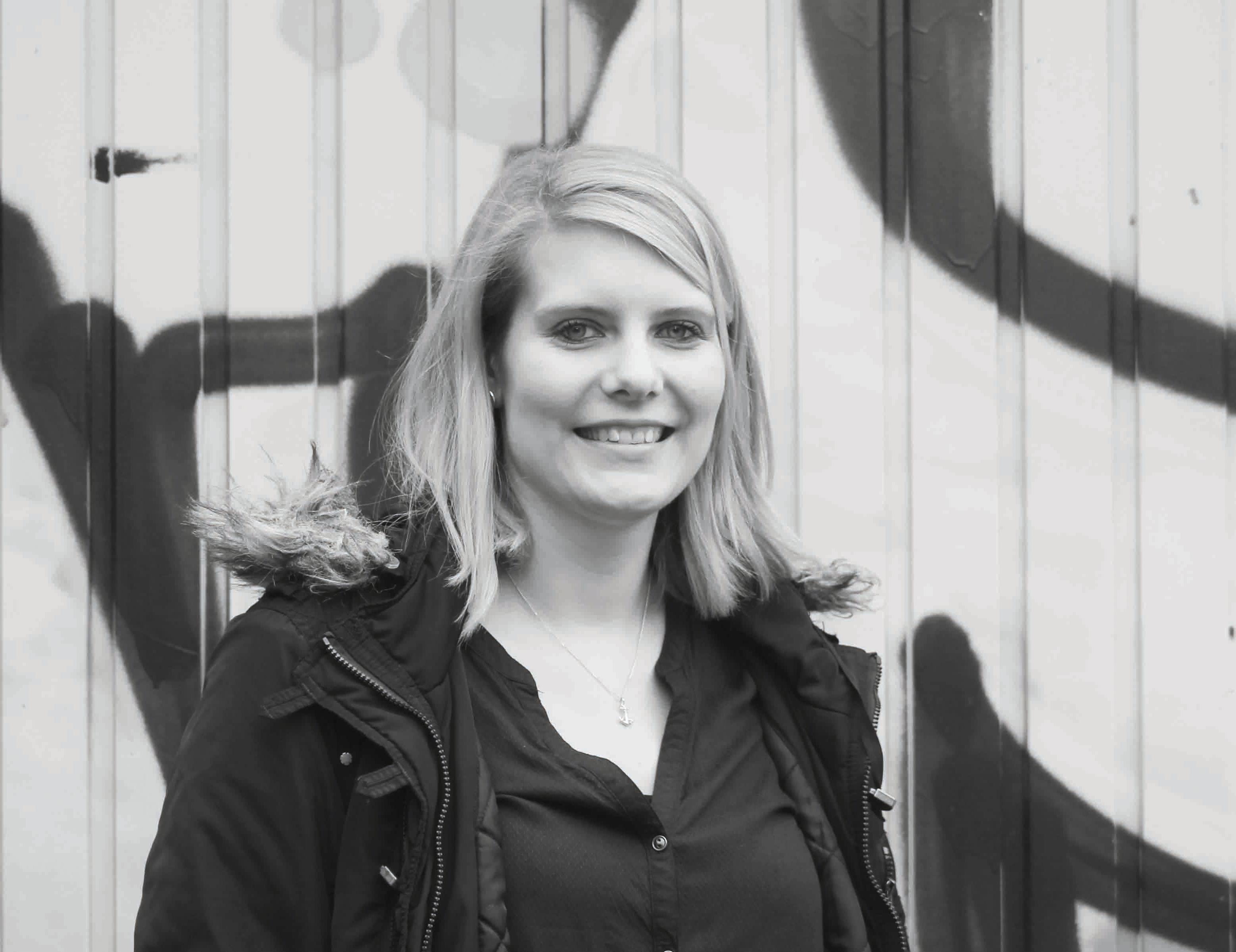 Eine blonde junge Frau steht vpr einer Wand und lächelt.