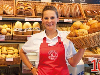 Eine junge Frau steht, einen Brotkorb haltend, lächeln hinter dem Tresen einer Backstube.