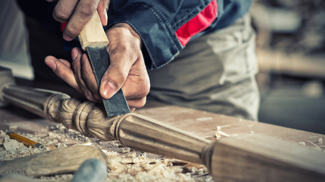 Eine Person bearbeitet ein Stück Holz.
