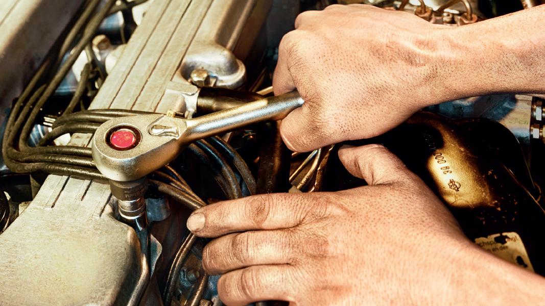 Zwei Hände schrauben an einem Motor herum.