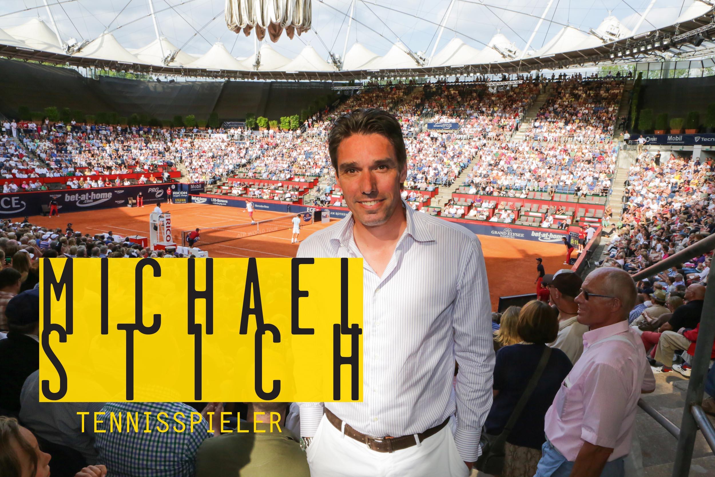 Ein Tennisspieler steht in einem Stadion und lächelt in die Kamera.