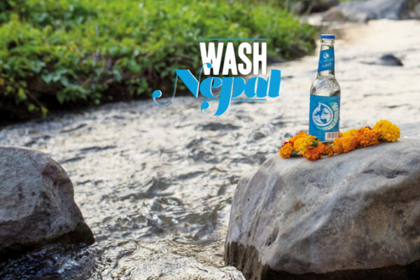 """Eine Flasche steht auf einem Felsen in einem Fluß. Ein Schriftzug mit """"Vivia con agua"""" befindet sich daneben."""""""