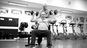 Fotostrecke Teil 3: Ein Mann unterstützt einen anderen mann beim Krafttraining.