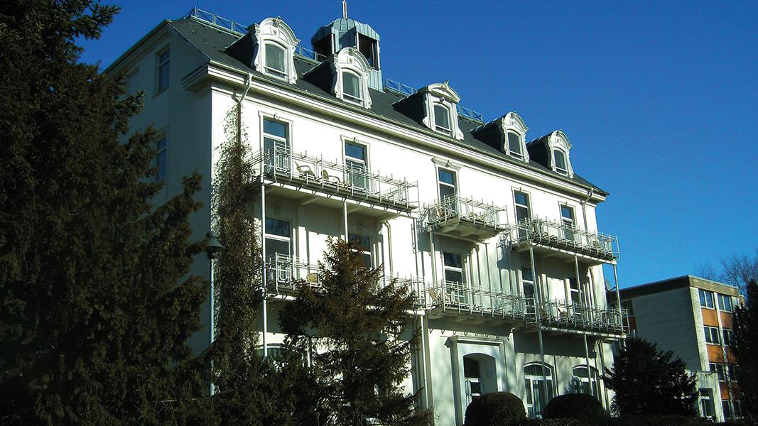 Ein dreistöckiges Haus mit heller Fassade unter blauem Himmel.