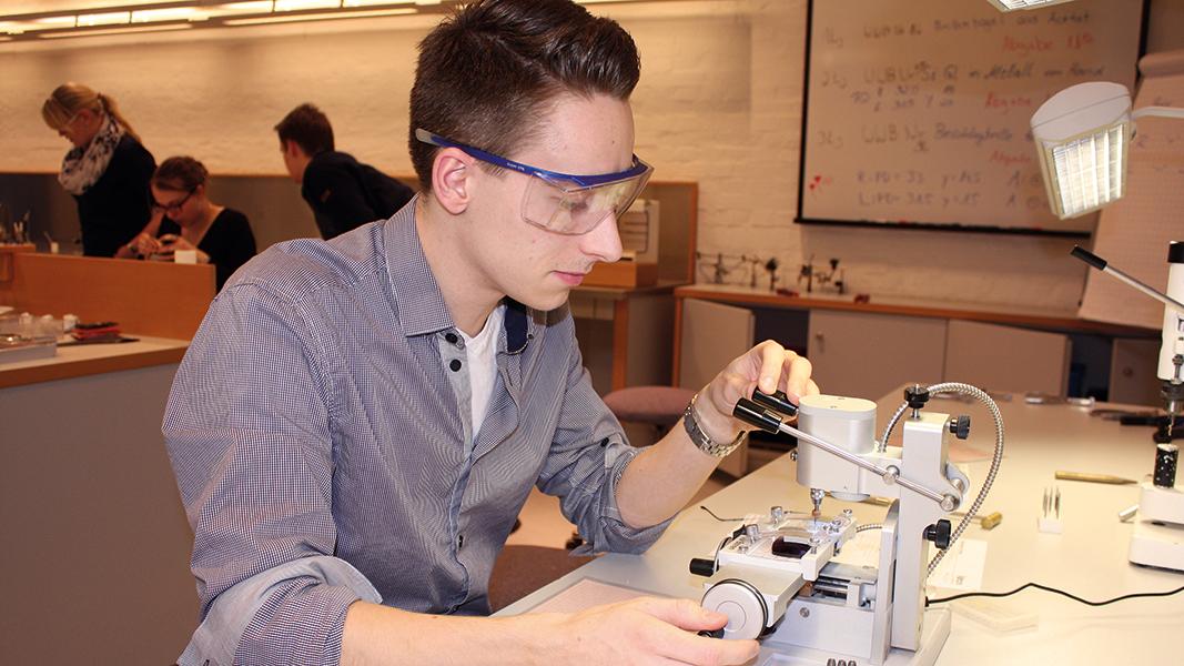 Ein junger Mann sitz mit Schutzbrille an einem Tisch.