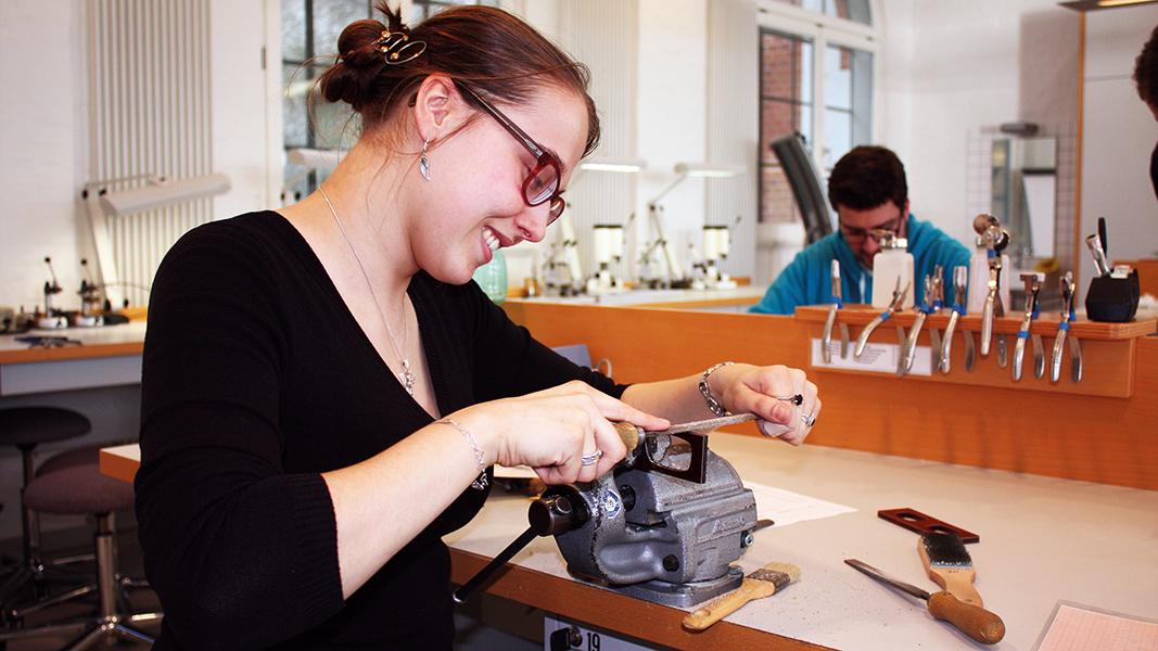 Eine bebrillte junge Frau sitzt an einer Werkbank und lächelt.