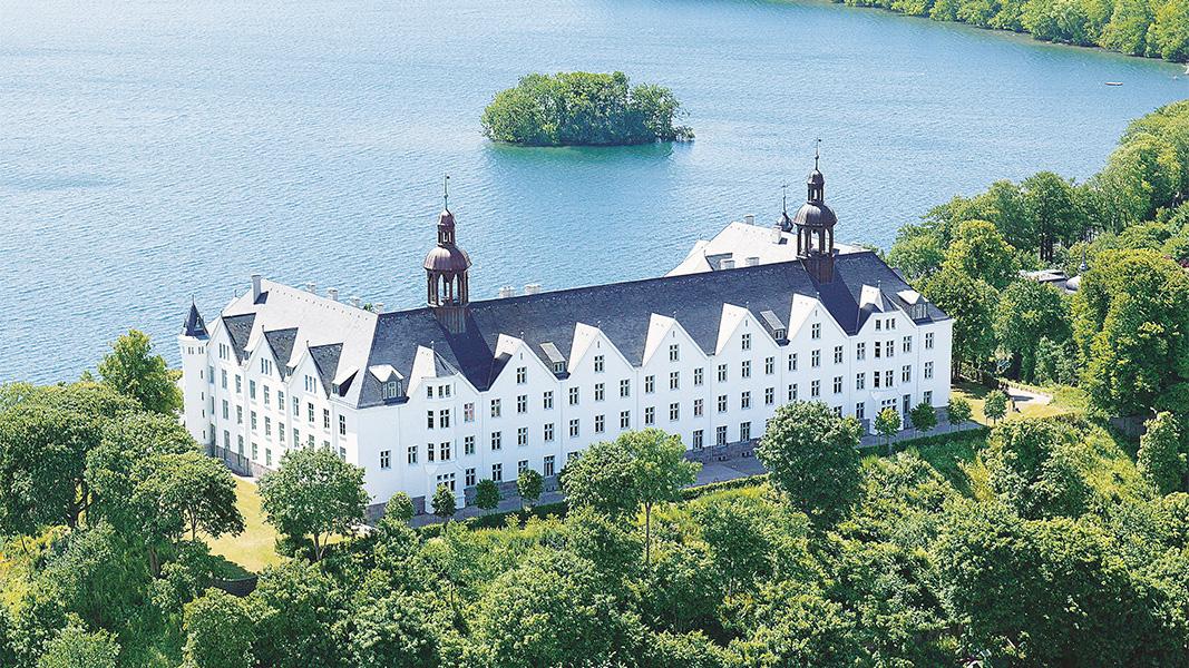 Ein weißes Schloss an einem See.