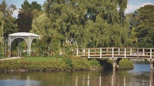 Auf einem Teich ist eine Insel mit einem Pavillon zu sehen. Zur Insel führt eine Brücke.