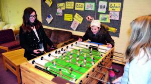 Schülerinnen und Schüler spielen an einem Tischkicker.