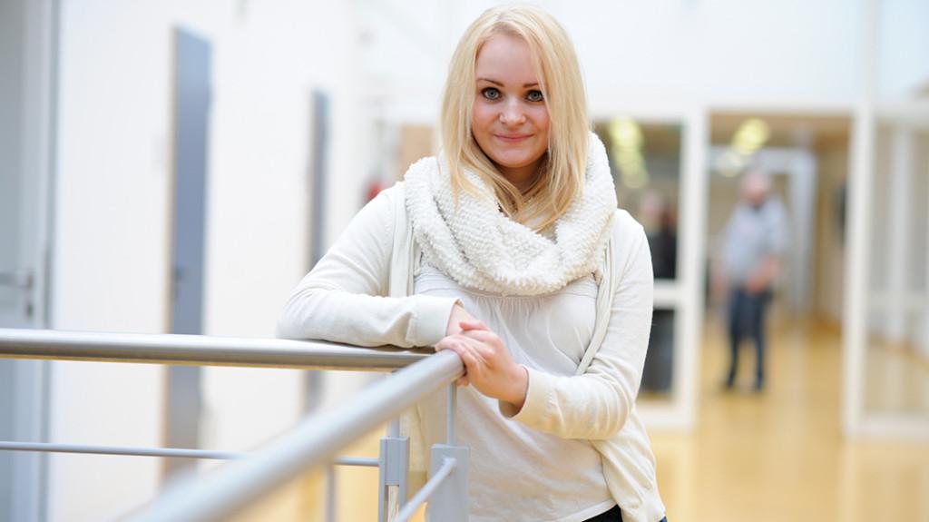 Eine blonde junge Frau in weißer Kleidung lehnt an einem Geländer und lächelt in die Kamera.